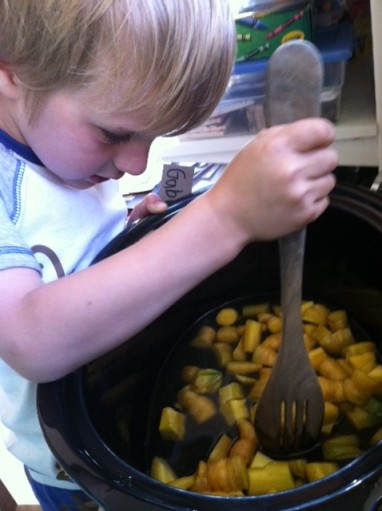 My son making a dish of his own creation (in the slow-cooker) with just-picked carrots and maple syrup